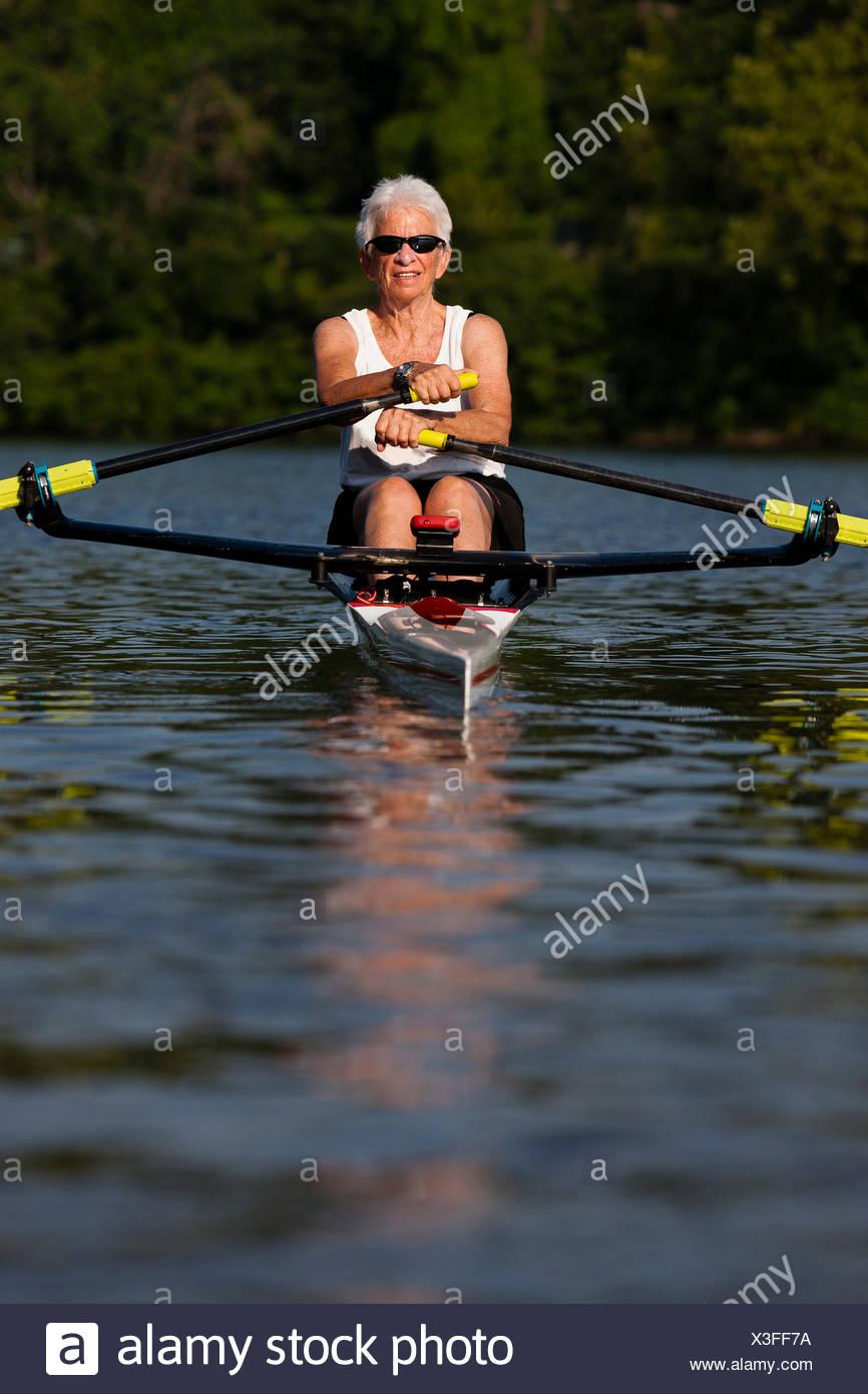 Senior woman rowing en bateau à rames Photo Stock