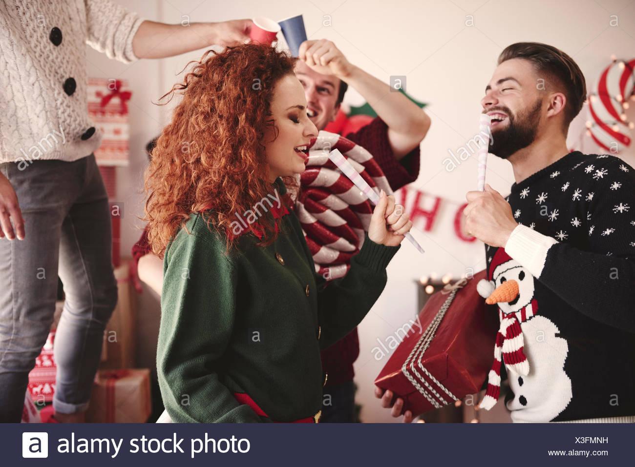 Jeune homme et femme chantant avec microphones prétendre at Christmas party Photo Stock