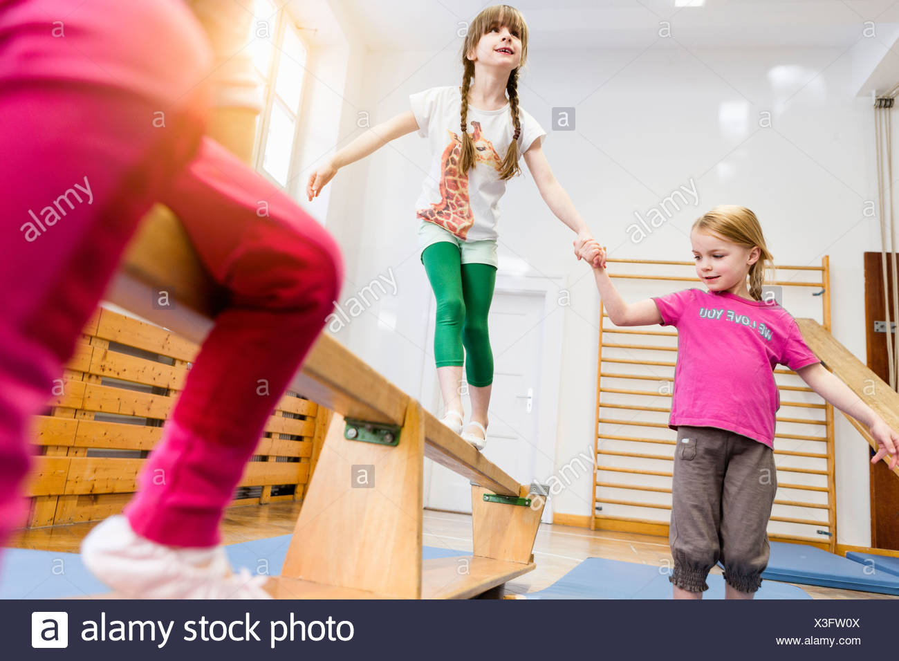 Girl holding hands aider ami en poutre, ami en premier plan Photo Stock