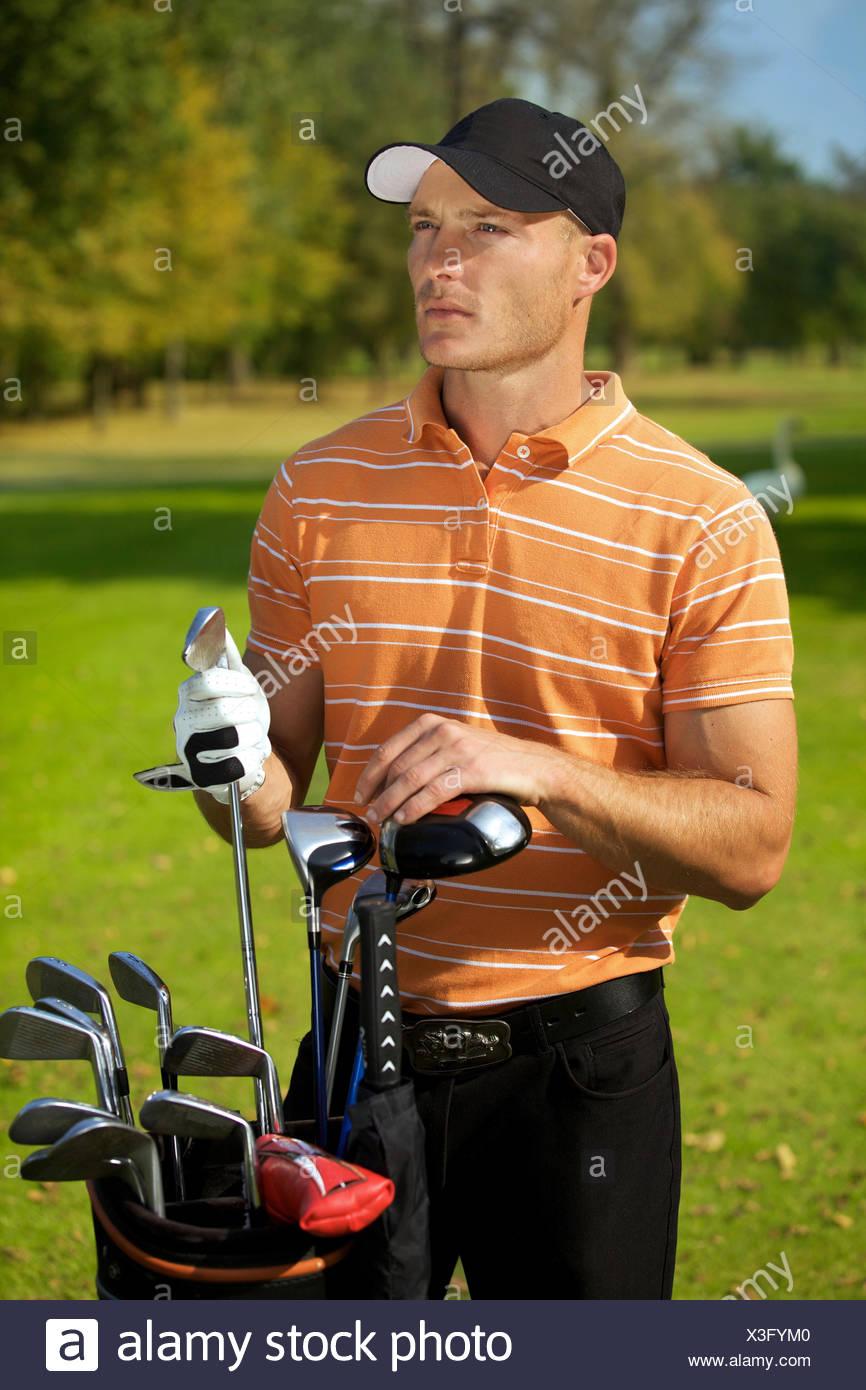 Jeune homme debout par golf sac plein de bâtons Photo Stock