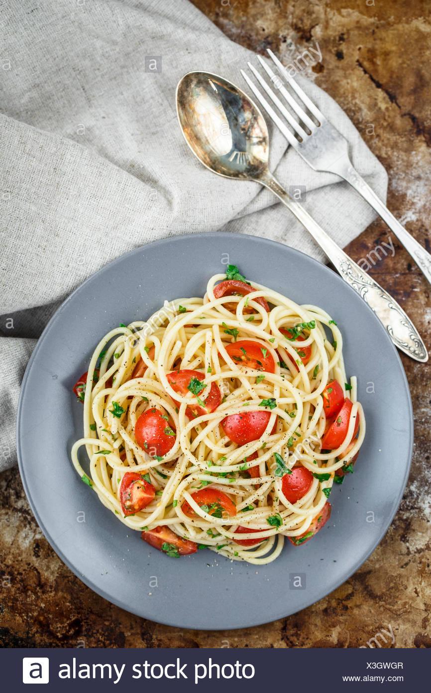 Les pâtes Spaghetti aux tomates cerises et le persil sur arrière-plan rustric Photo Stock