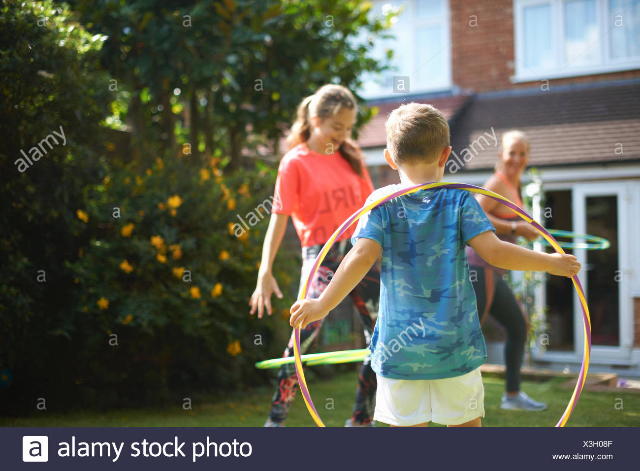 Garçon regardant mère et sœur adolescente hoola hoop dans jardin Banque D'Images