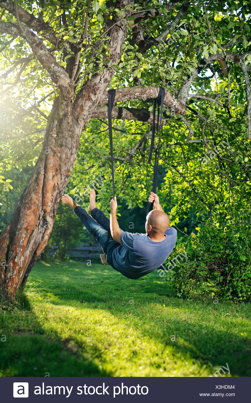 L'homme se balançant sur tree swing Photo Stock
