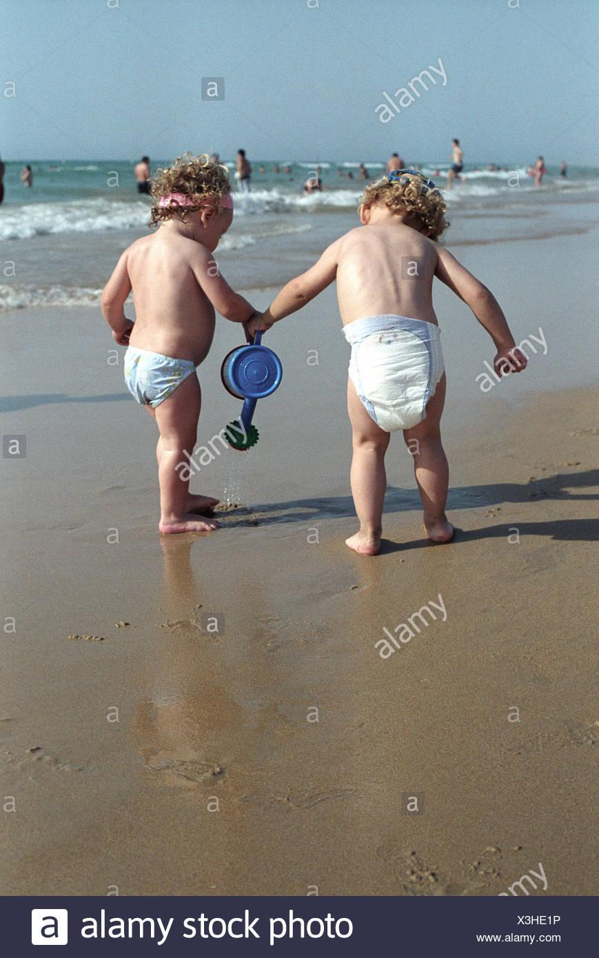 Petit garçon et petite fille à jouer ensemble sur la plage Banque D'Images