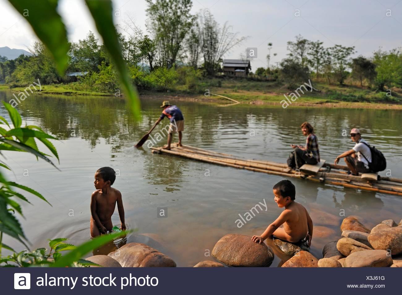 deux enfants jouant au bord de l 39 eau en radeau de bambou pour traverser la rivi re nam pak. Black Bedroom Furniture Sets. Home Design Ideas