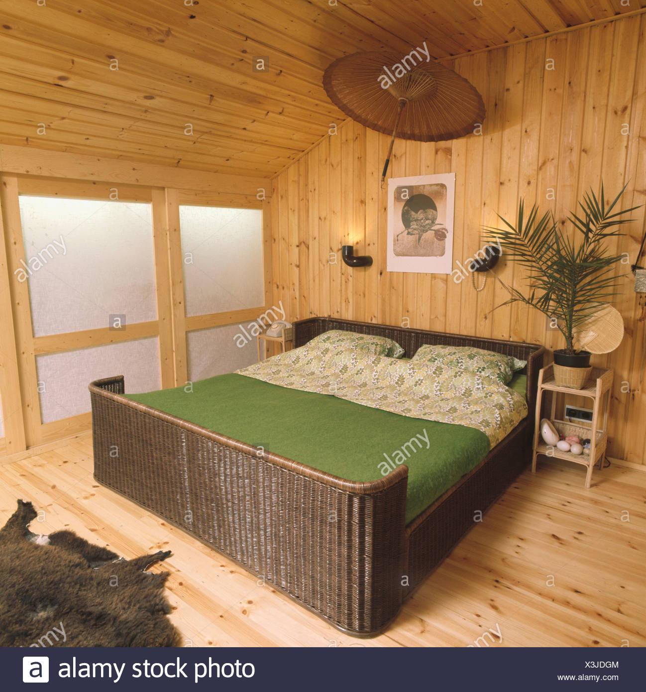 couvercle en osier vert sur lit de 70 chambre avec lambris et