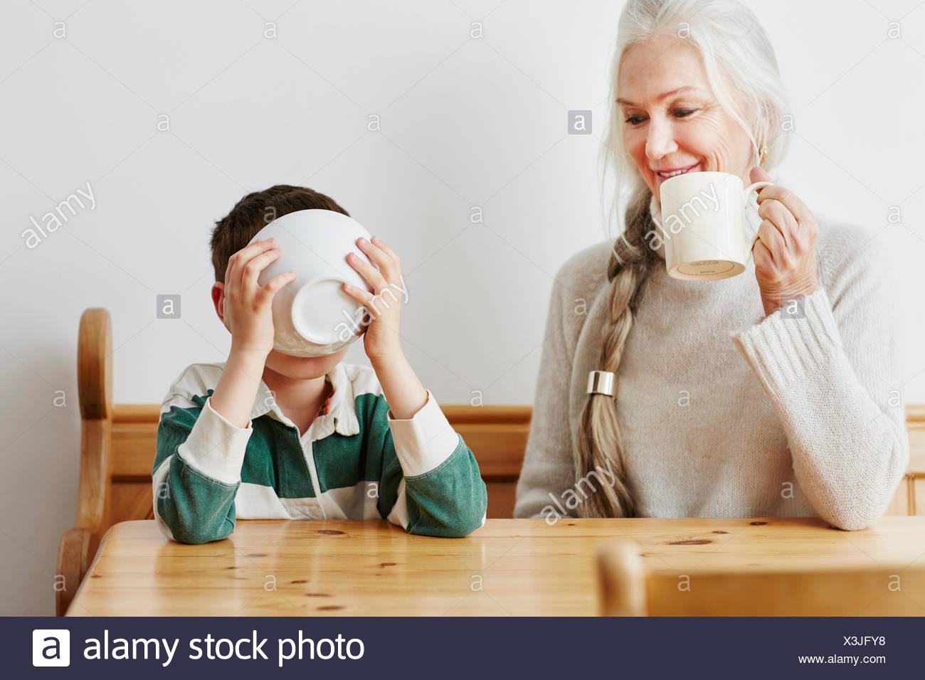 Boy boire du lait à partir de la cuvette avec grand-mère Photo Stock