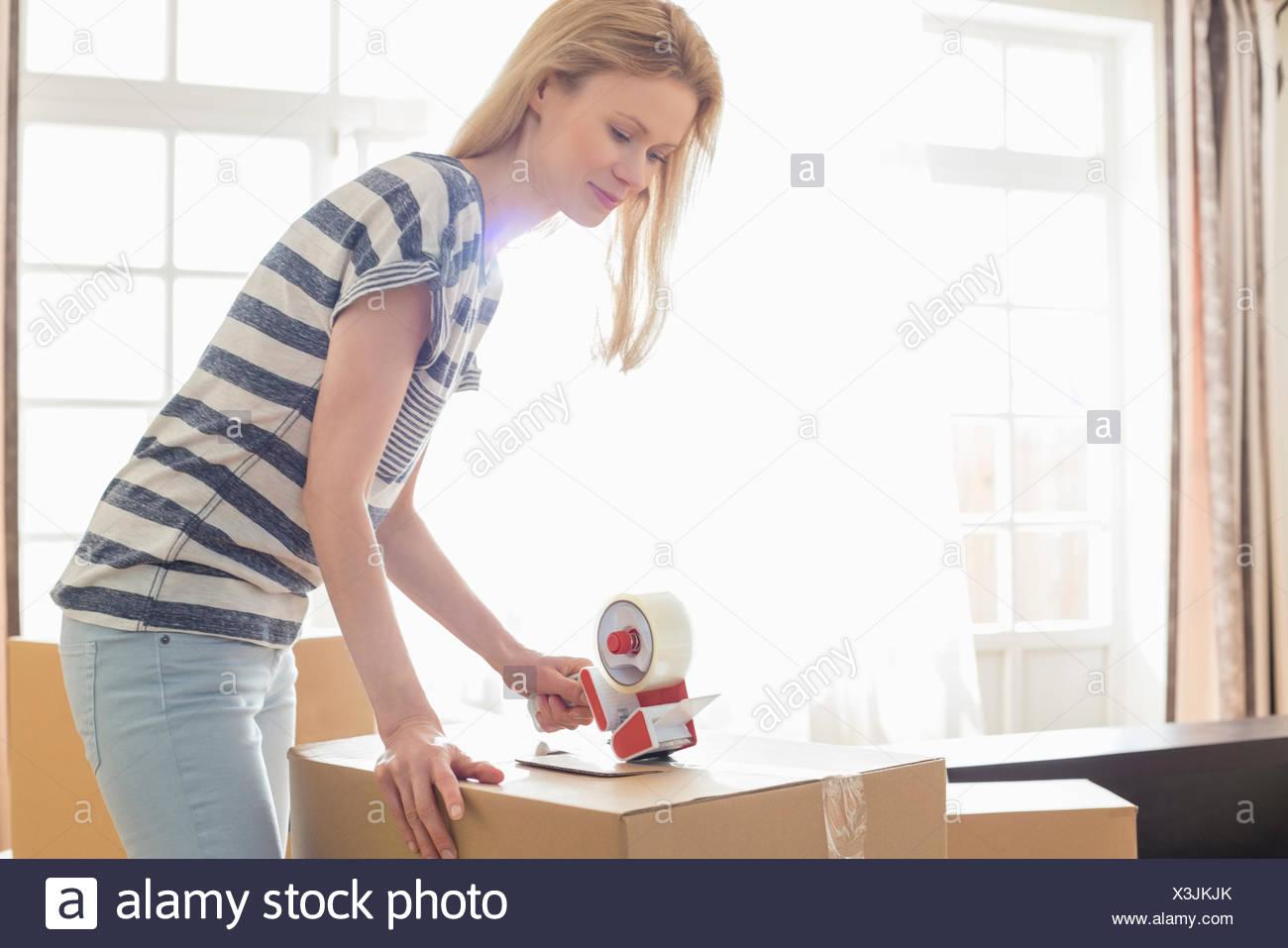 Woman packing déménagement fort à la maison Photo Stock