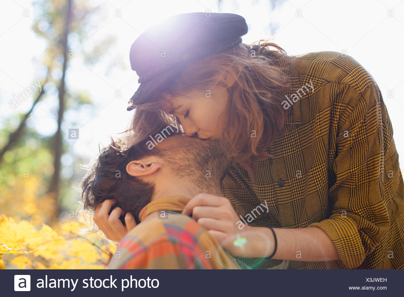Happy young couple kissing in a park Banque D'Images