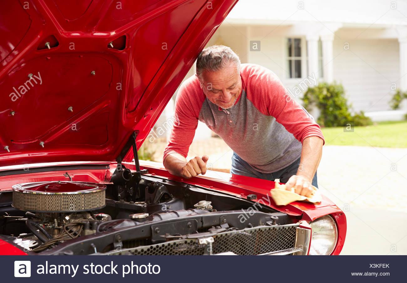 Homme supérieurs à la retraite restauré nettoyage voiture classique Photo Stock