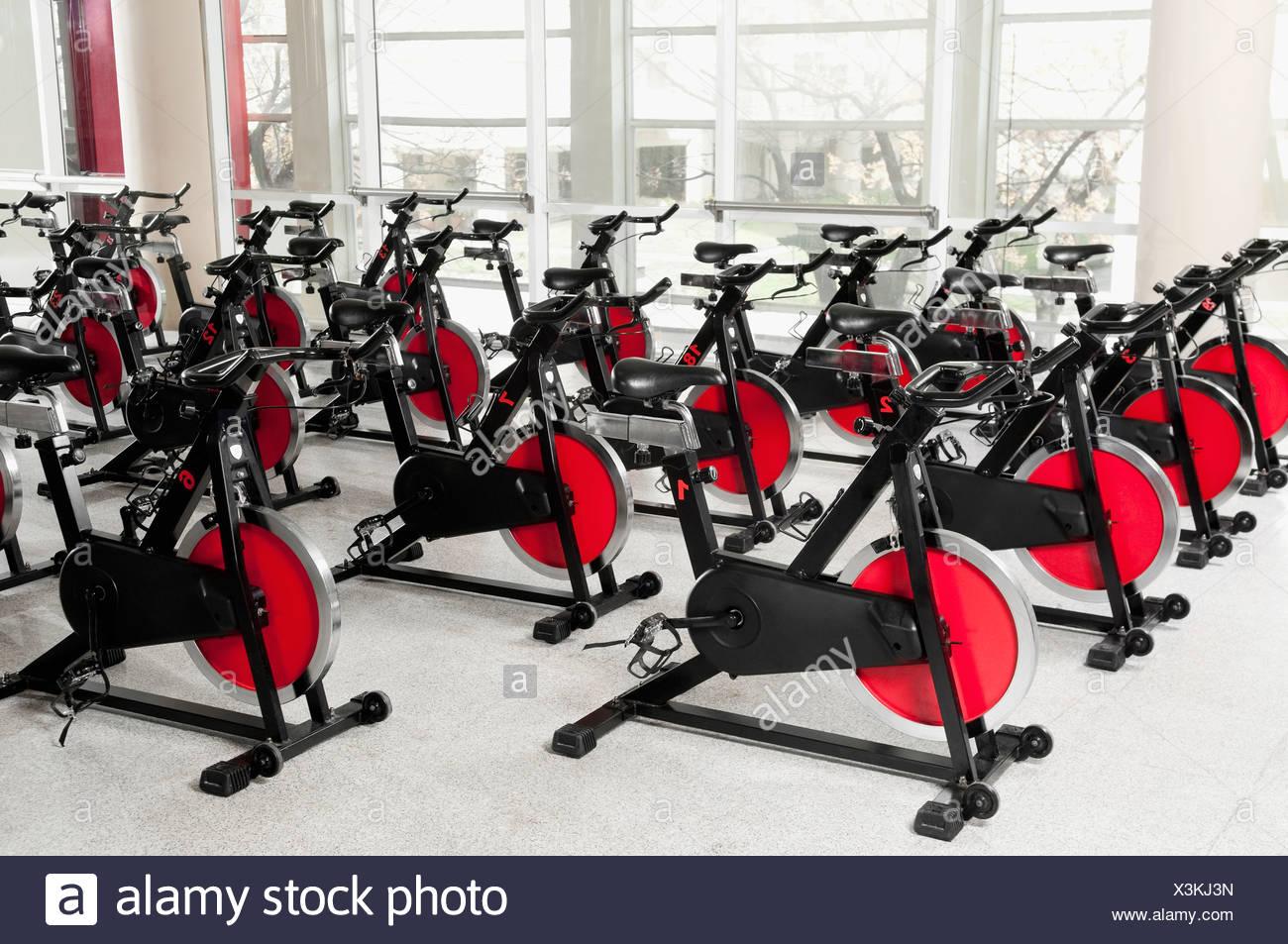 Vélos d'exercice dans une salle de sport Photo Stock