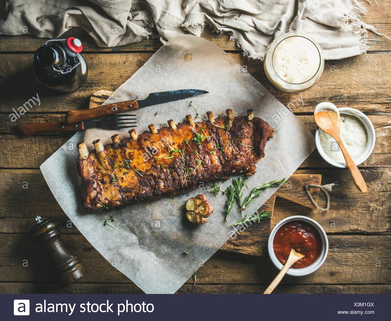 Côtes de porc grillées partiellement coupé en morceaux sur papier cuisson avec l'ail, le romarin, le ketchup, la sauce à l'ail et de bière brune sur rustic Photo Stock