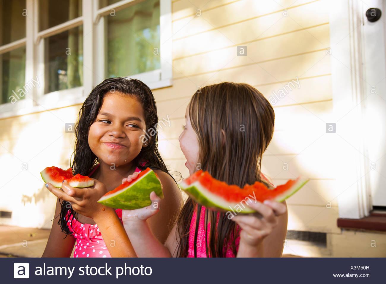 Deux filles souriant assis sur le porche de la chambre avec des tranches de melon d'eau Photo Stock