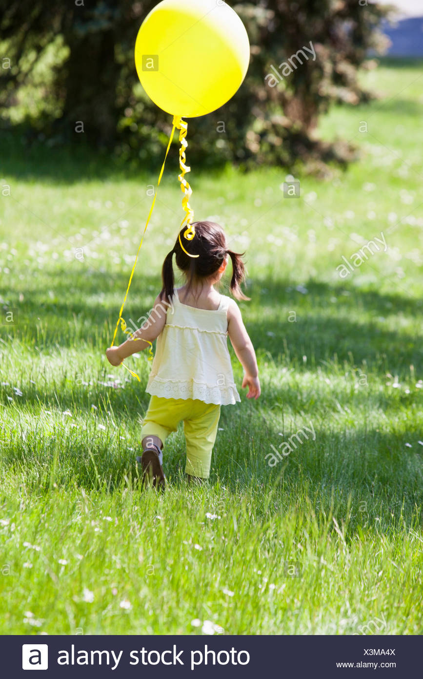 Bord de ballons fille in backyard Photo Stock