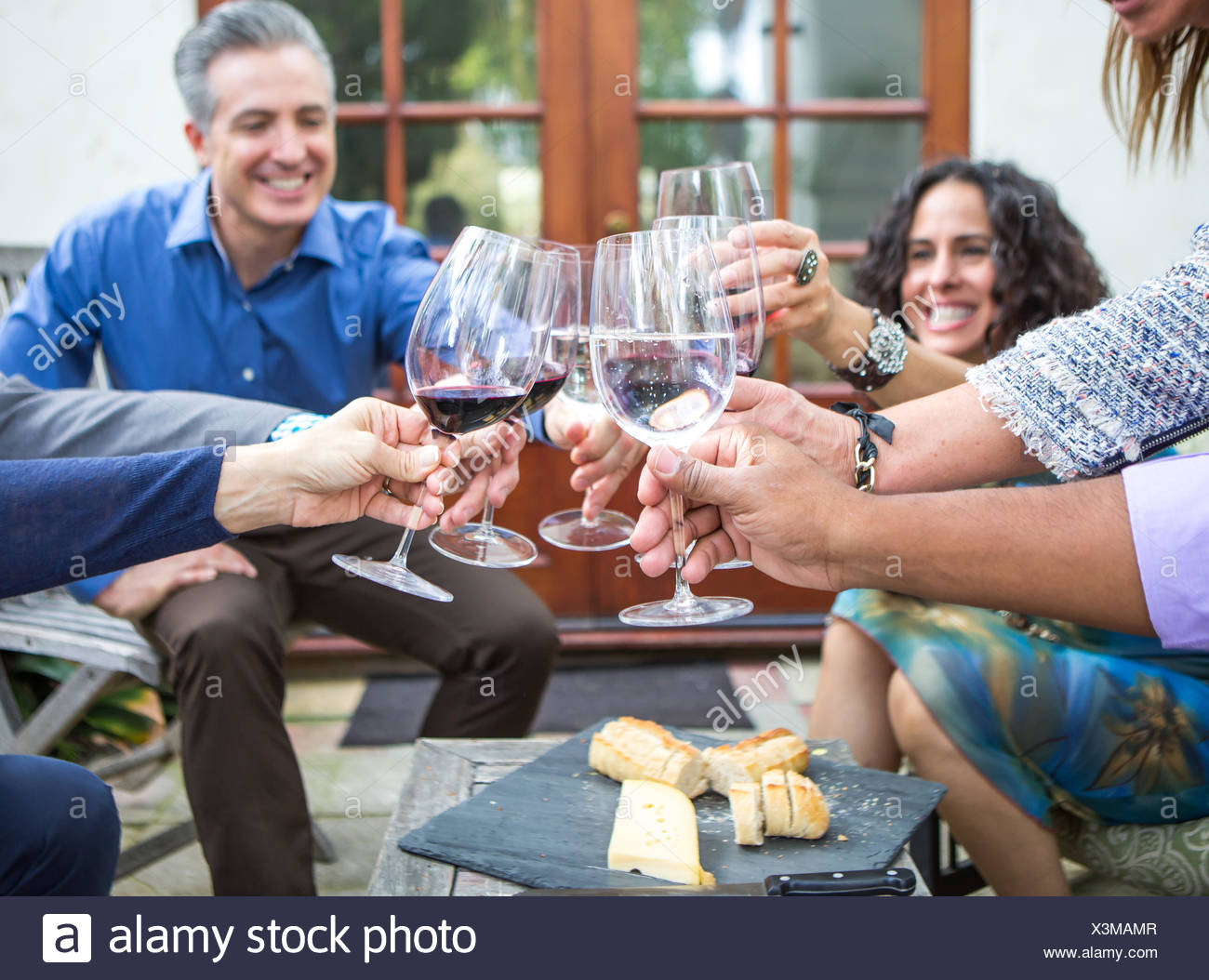 Les adultes les amis du vin toast at garden party on patio Photo Stock