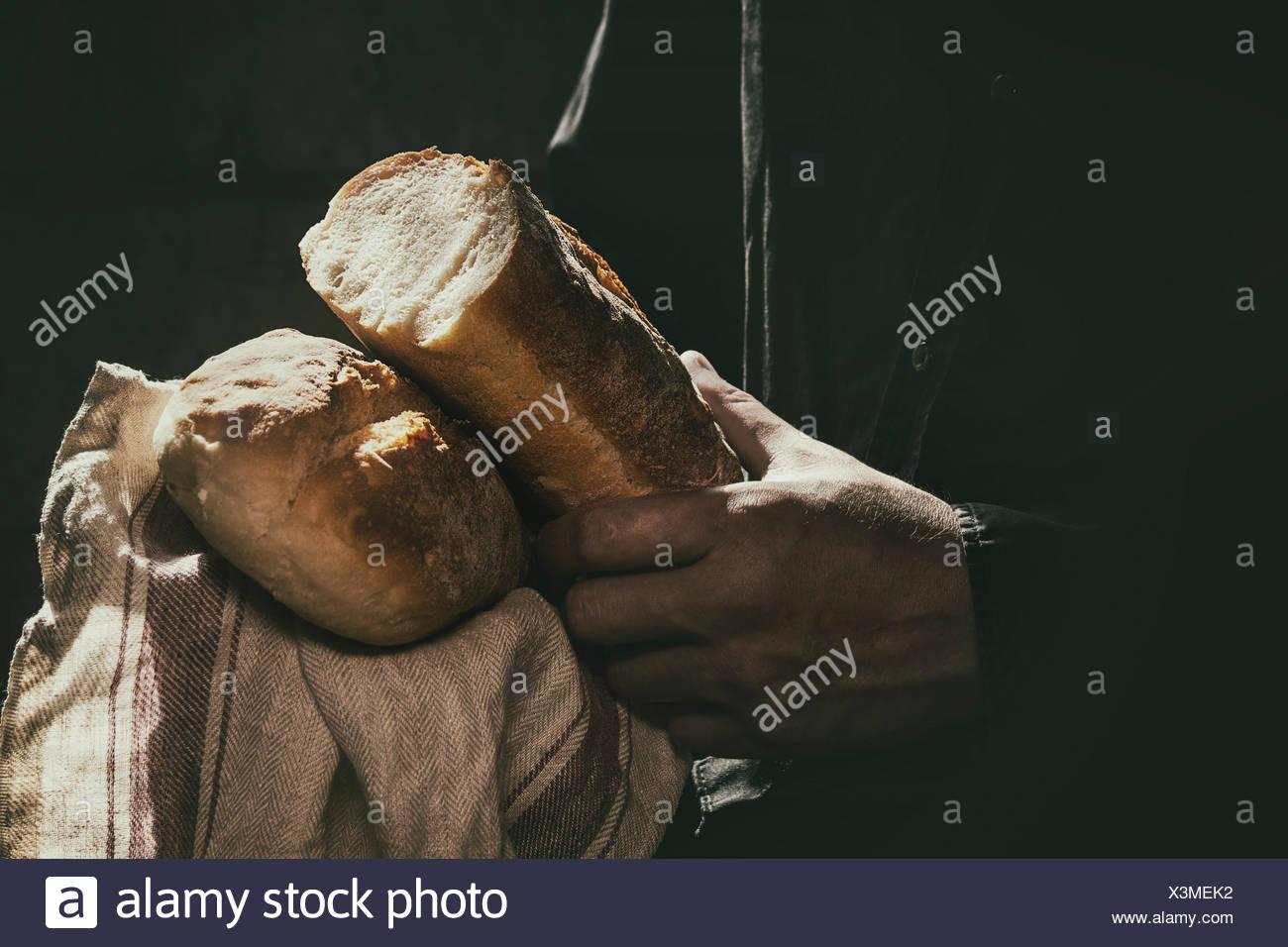 Miche de pain de blé frais entre les mains de l'homme dans le soleil. Lumière jour rustique dans une pièce sombre. Image tonique Photo Stock
