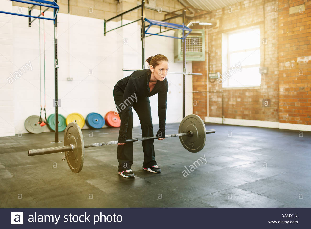 Woman lifting barbell in gym Photo Stock