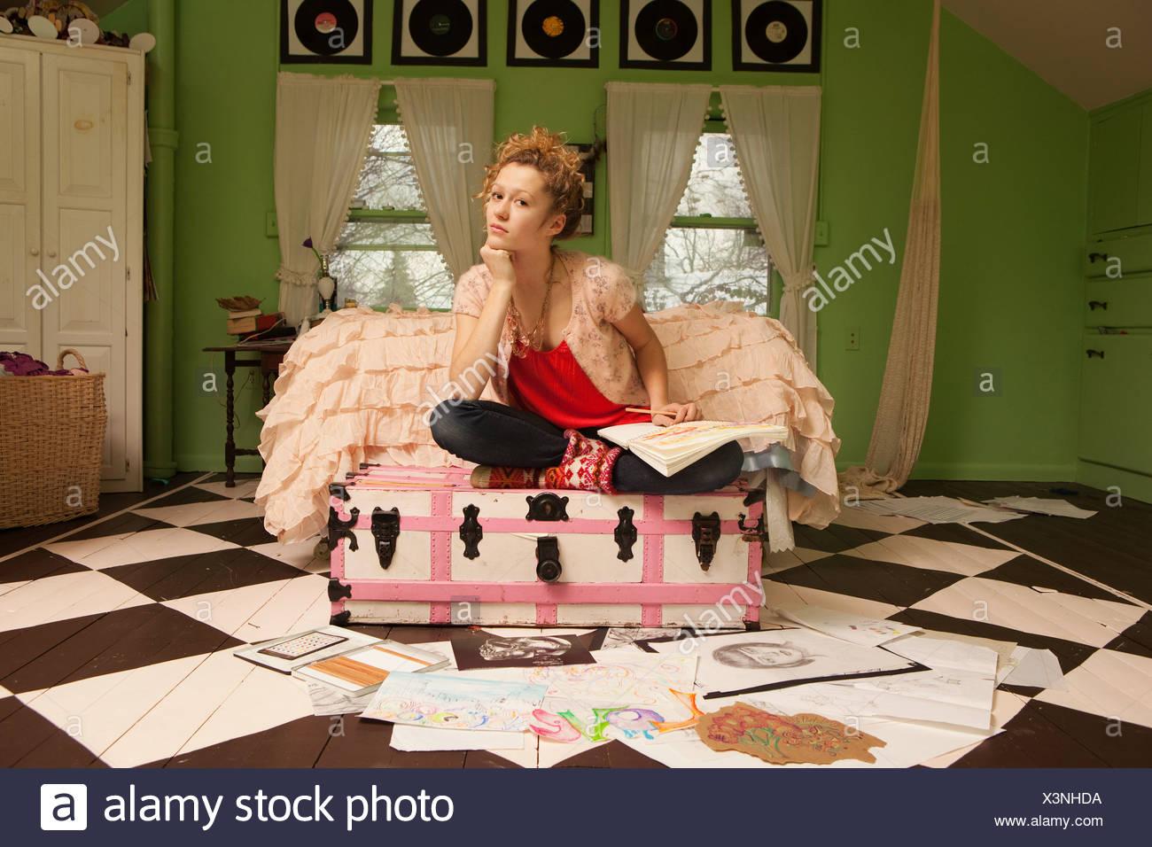 Teenage girl sitting on pouf avec des dessins sur plancher de chambre à coucher Photo Stock