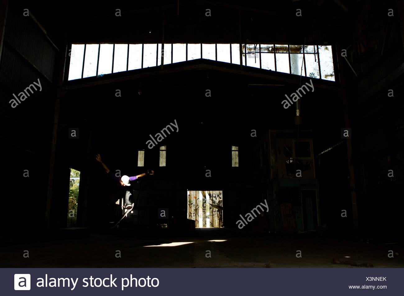 Un skater ollies dans un entrepôt abandonné sur la côte centrale, New South Wales, Australie. Photo Stock