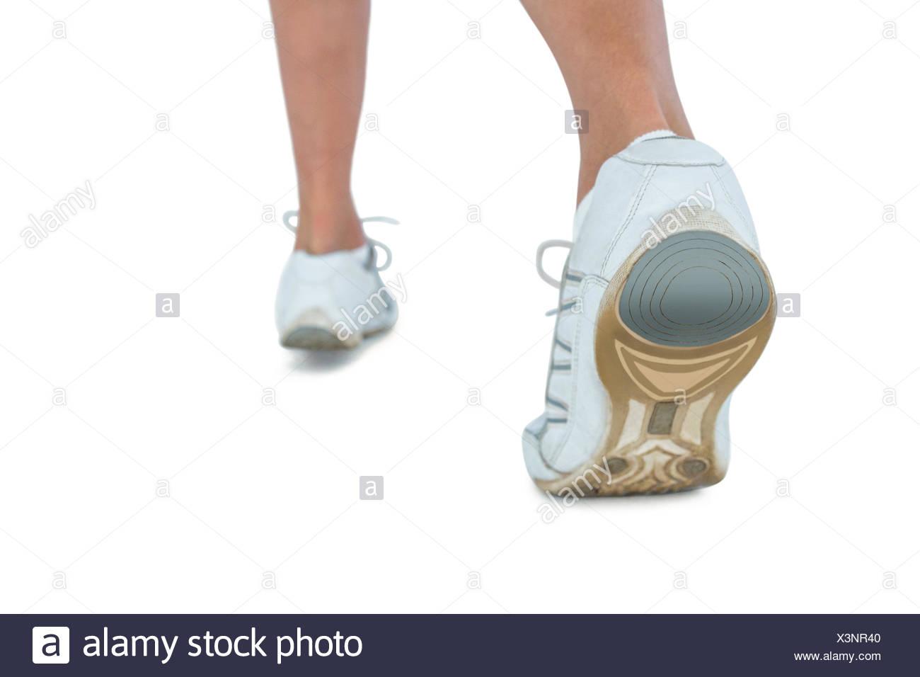 La section basse de femme portant la chaussure de sport le jogging Photo Stock