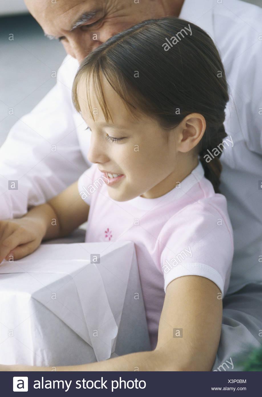 Girl holding présent pendant que grand-père regarde par-dessus son épaule Photo Stock