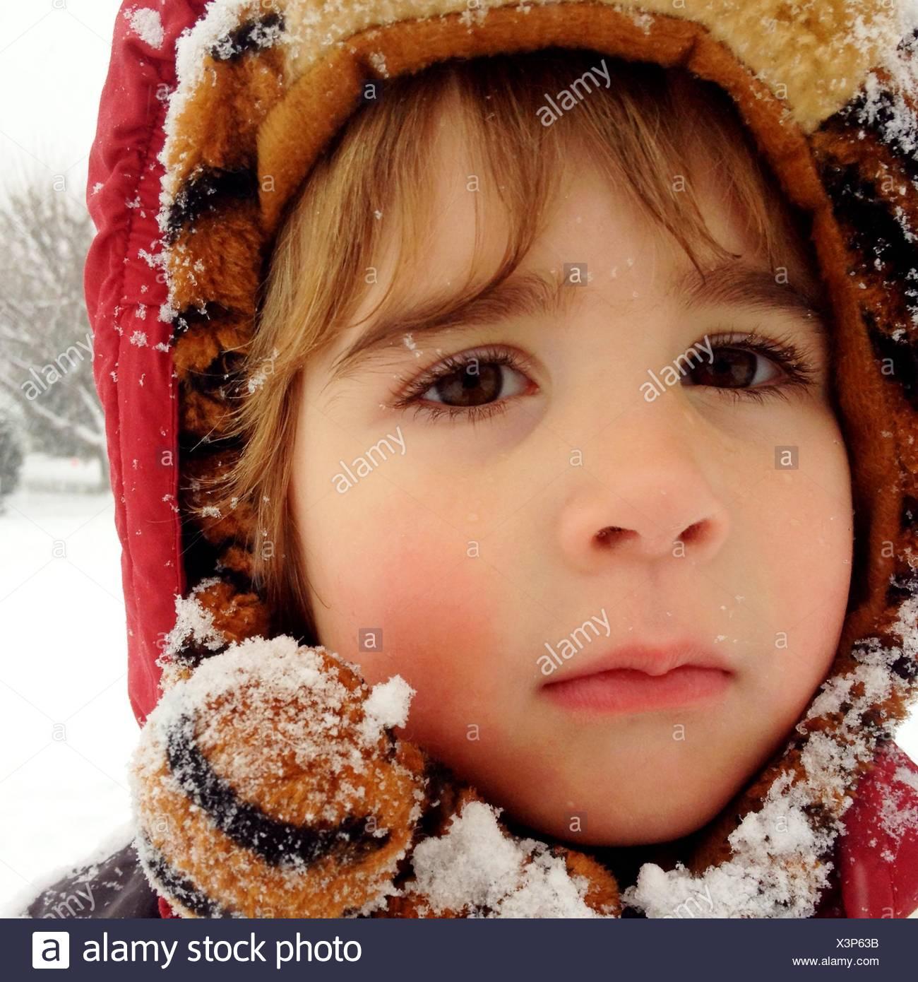 Portrait d'un jeune garçon portant des vêtements d'hiver à capuchon saupoudré de neige Photo Stock
