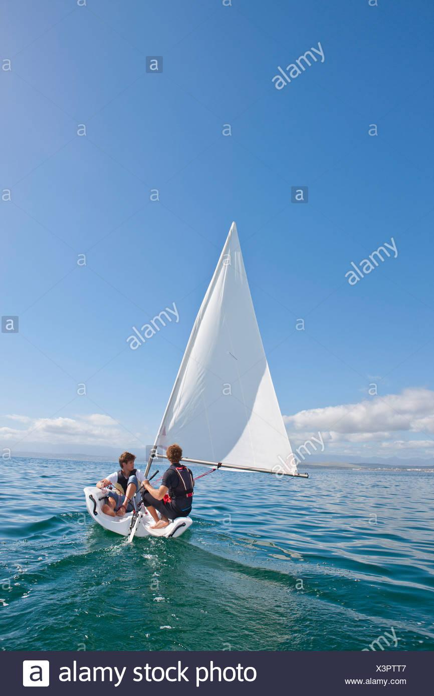 Deux jeunes hommes de la voile en mer Photo Stock