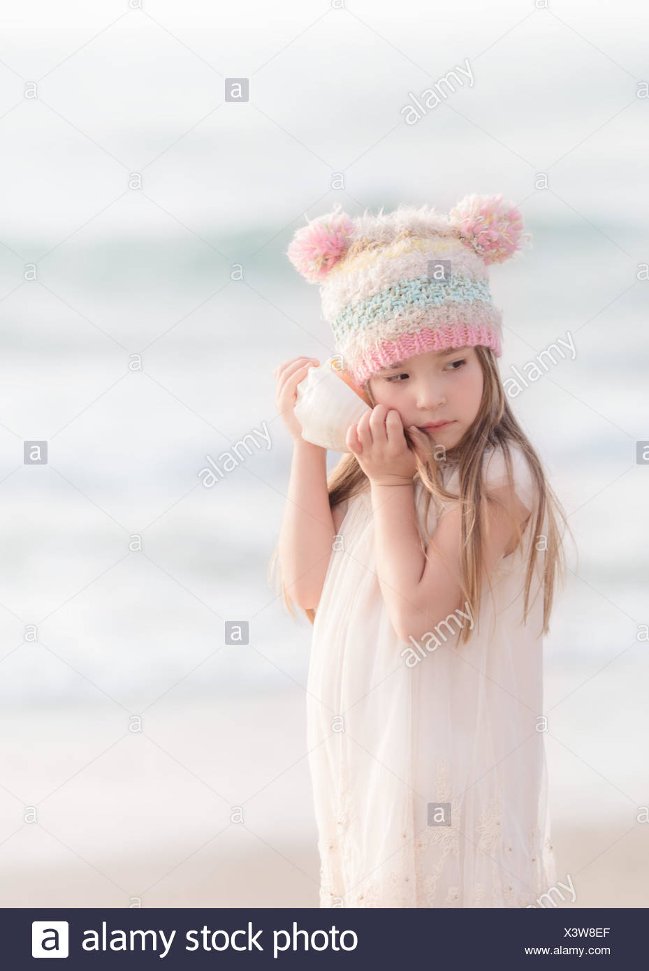 Girl standing on beach l'écoute d'un coquillage Photo Stock