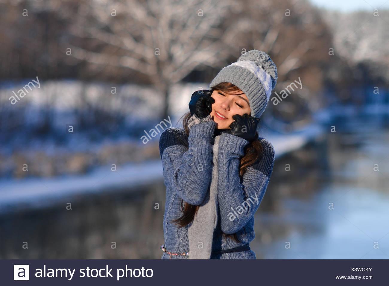 Photo de fermé les yeux sourire ensoleillé belle fille mignonne bénéficiant  d une nature d hiver sur fond d hiver forêt enneigée. Portrait de jeune  fille en ... 7c3e69d8f48