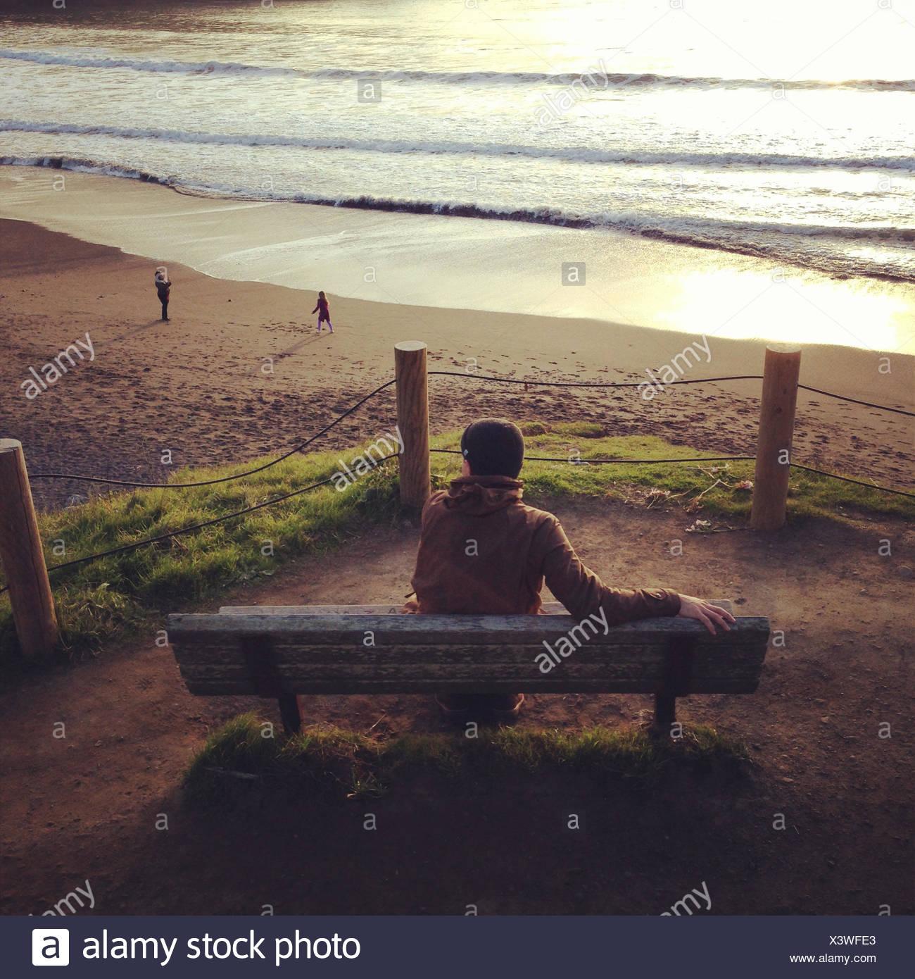 Homme assis sur un banc au coucher du soleil, Muir Beach, Marin, en Californie, l'Amérique, USA Photo Stock