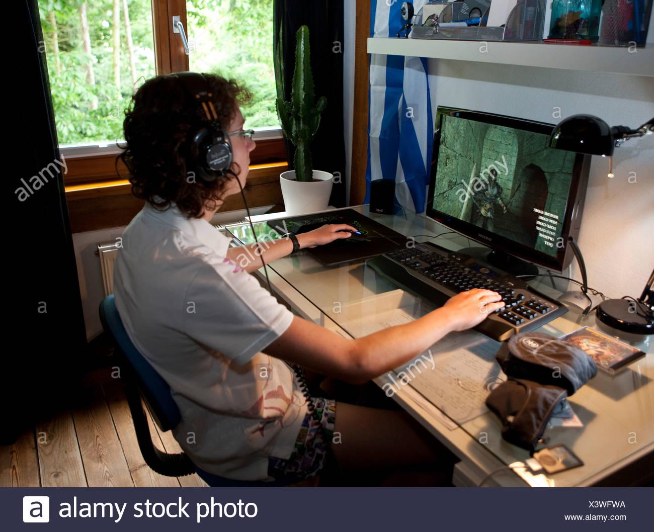 Un garçon, environ 15, jouant un jeu violent sur l'ordinateur dans sa chambre, l'Allemagne, de l'Europe Photo Stock