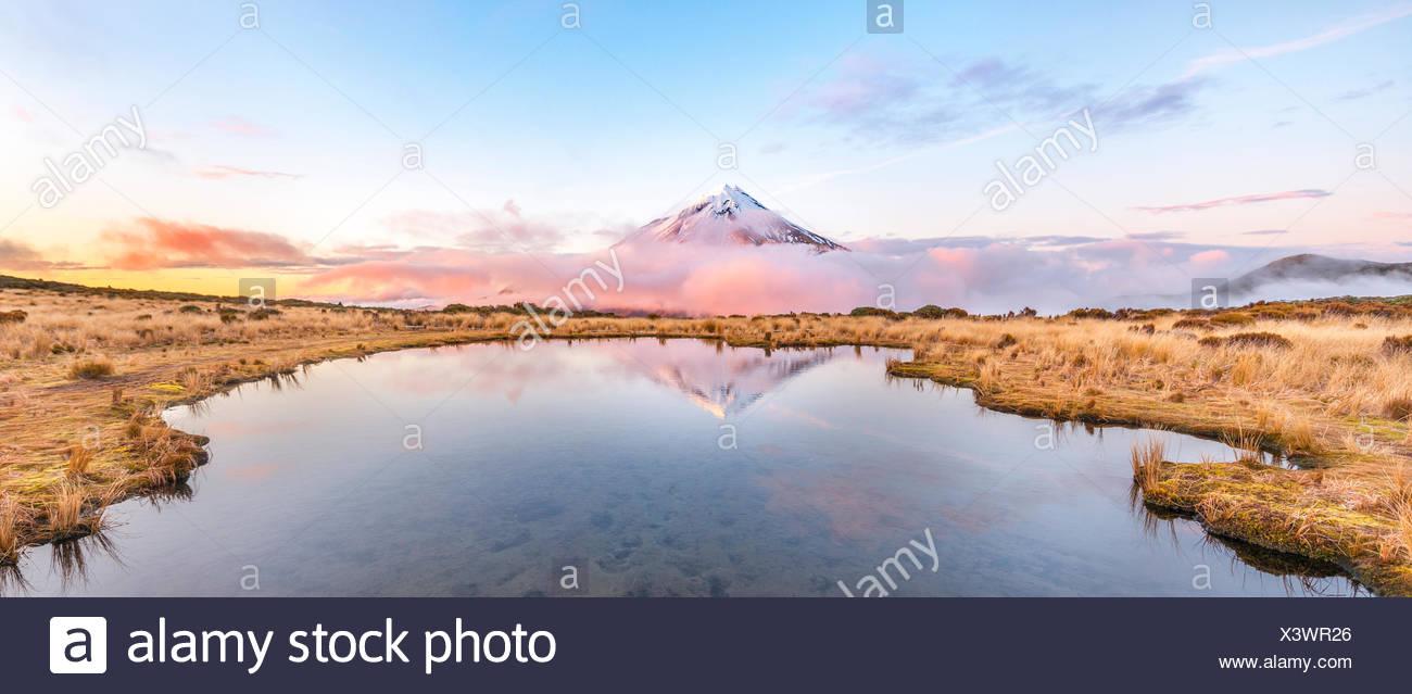 Reflet dans le lac rose Pouakai Tarn, nuages autour du Mont Taranaki ou Mont stratovolcan Egmont au coucher du soleil, Parc National d'Egmont Photo Stock
