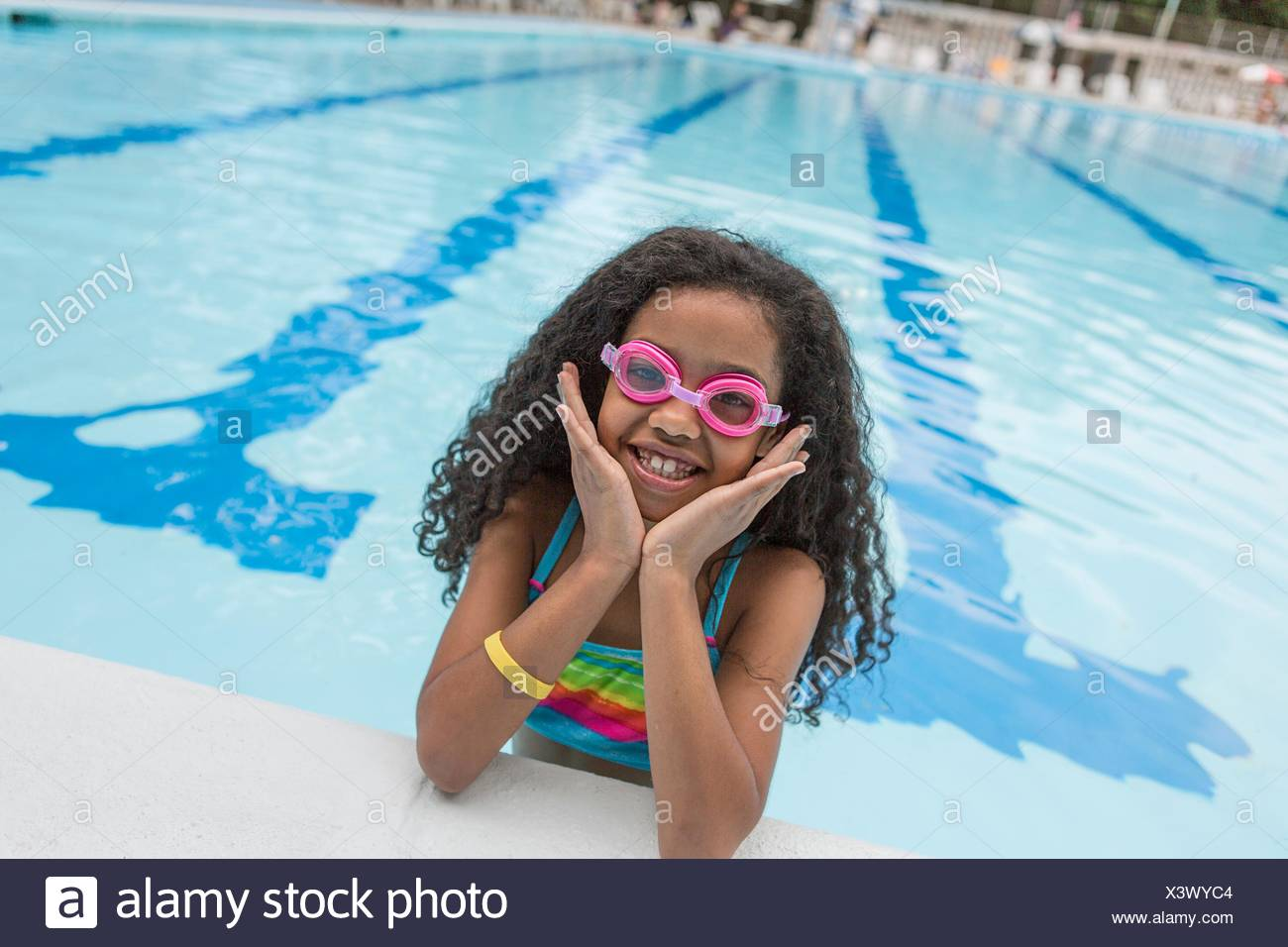 Portrait of Girl in swimming pool portant des lunettes de natation, smiling at camera Photo Stock