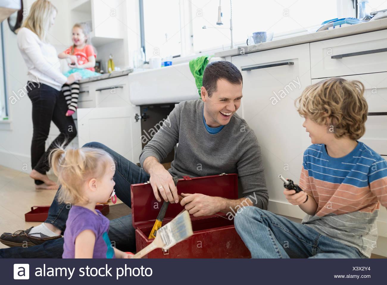 Le père et les enfants de rire sur le plancher de cuisine boîte à outils Photo Stock