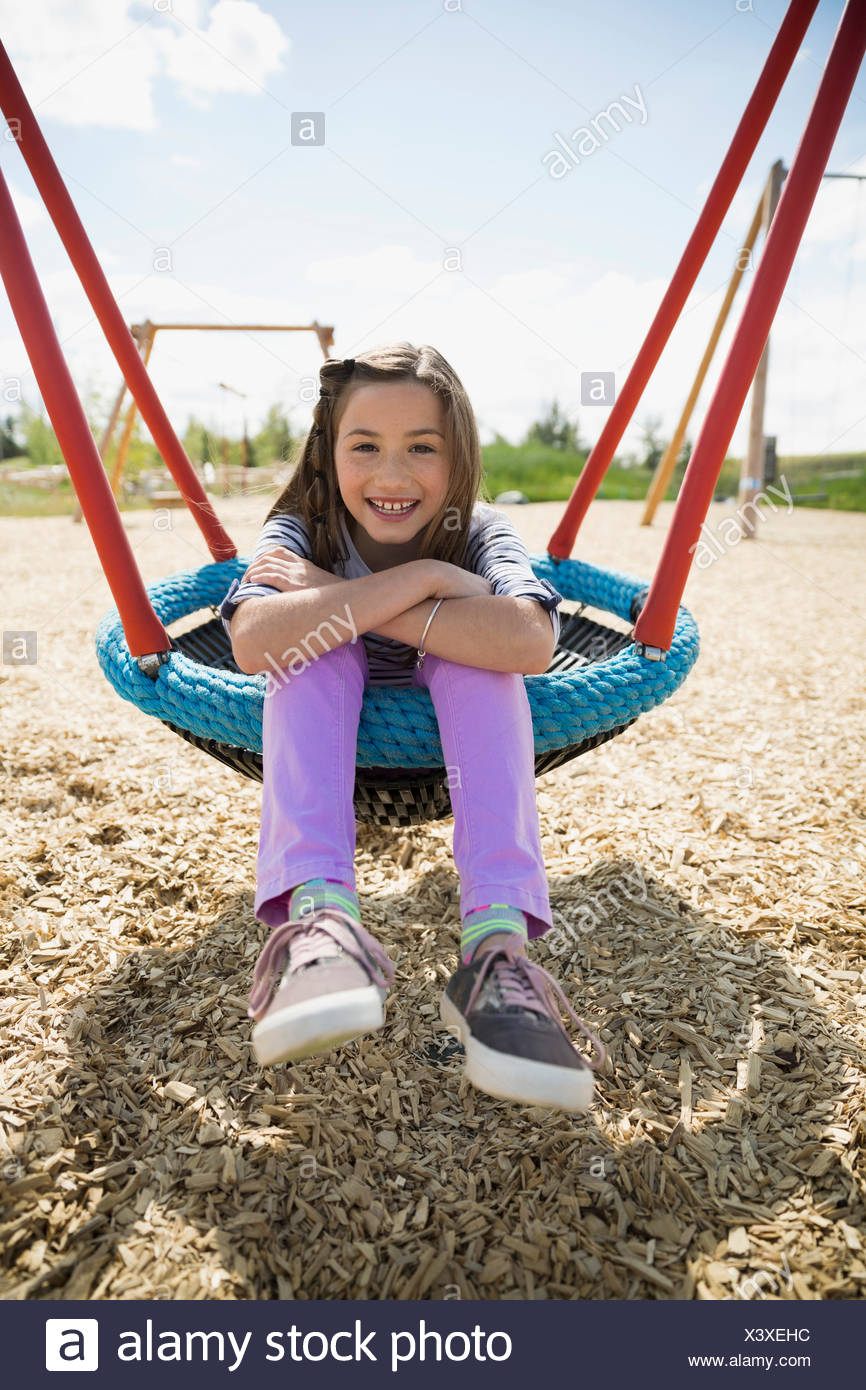 Portrait of smiling girl sitting in swing sunny jeux pour enfants Photo Stock