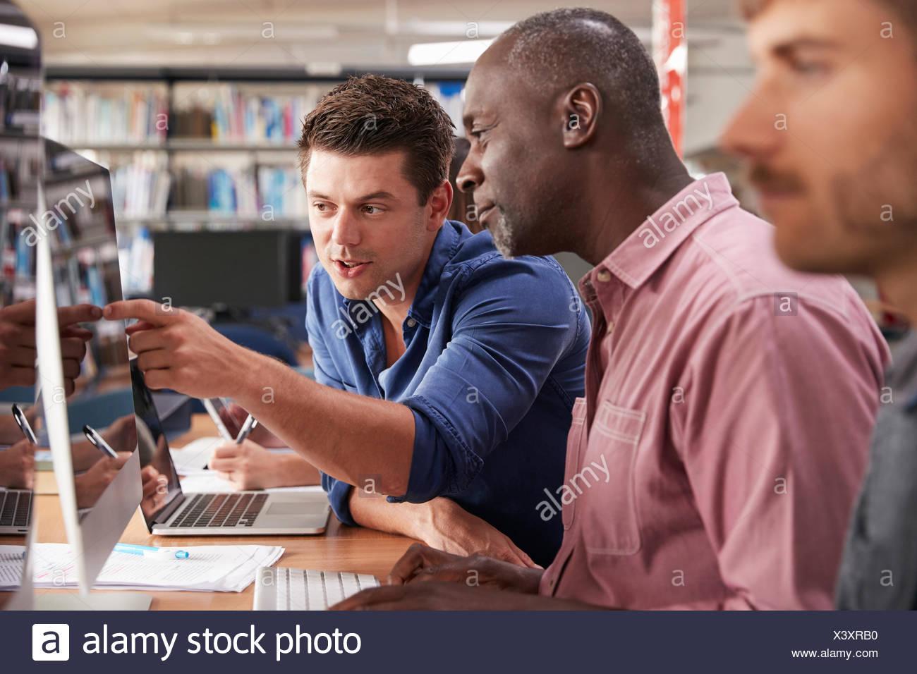 Mâle mature student avec tuteur l'acquisition de compétences en informatique Photo Stock