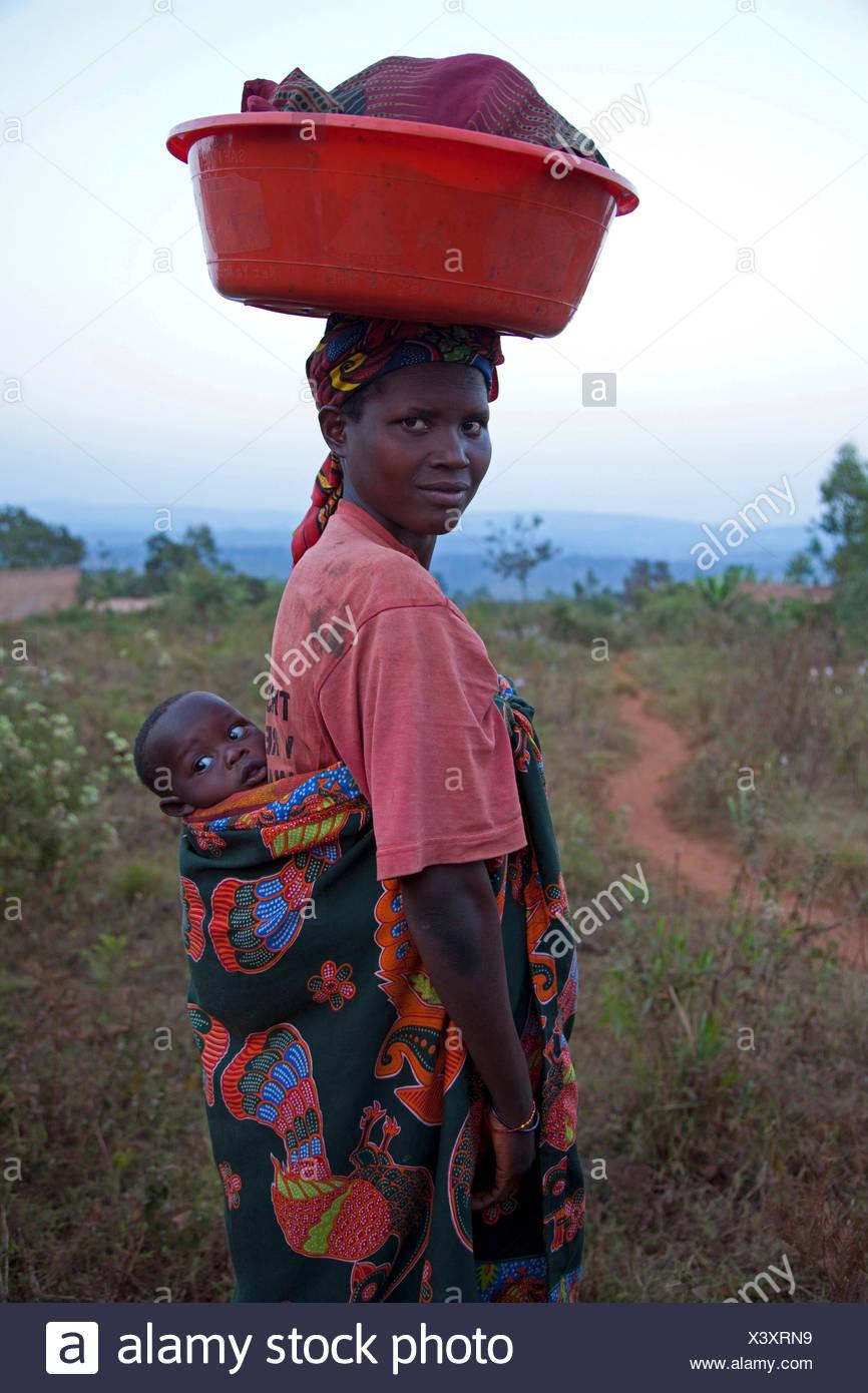 Maman avec bébé au dos du transport de lave sur sa tête, Burundi, Karuzi, Buhiga Photo Stock