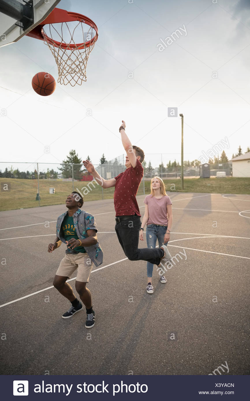 Amis adolescents jouant au basket-ball sur le terrain extérieur de basket-ball Photo Stock
