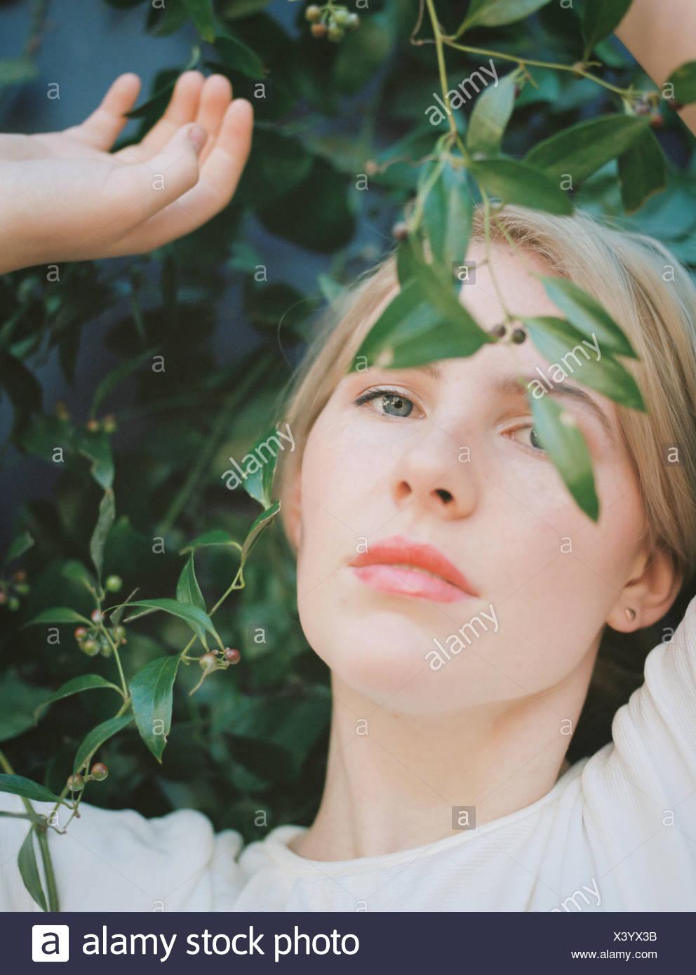 Une femme aux cheveux blonds à rêveusement à travers une vigne avec des feuilles vertes. Photo Stock