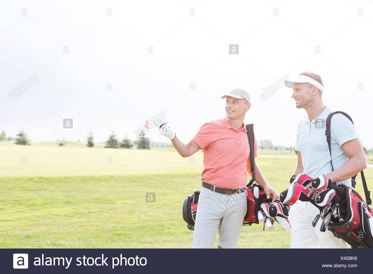 Homme montrant quelque chose à un ami au golf contre ciel clair Photo Stock