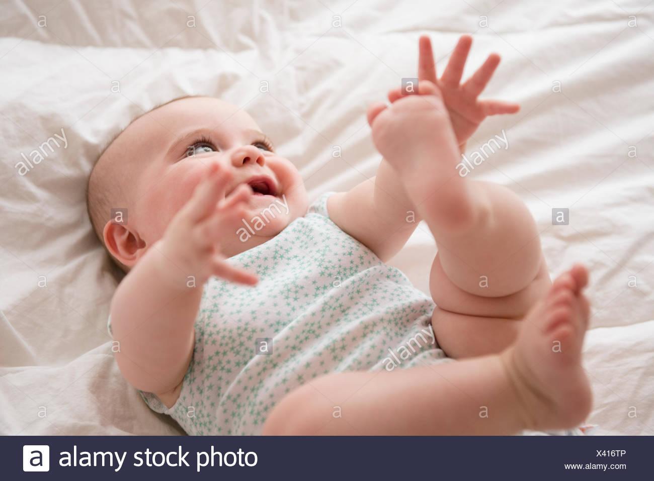 Baby Girl (12-17 mois) couché avec bras et jambes Photo Stock