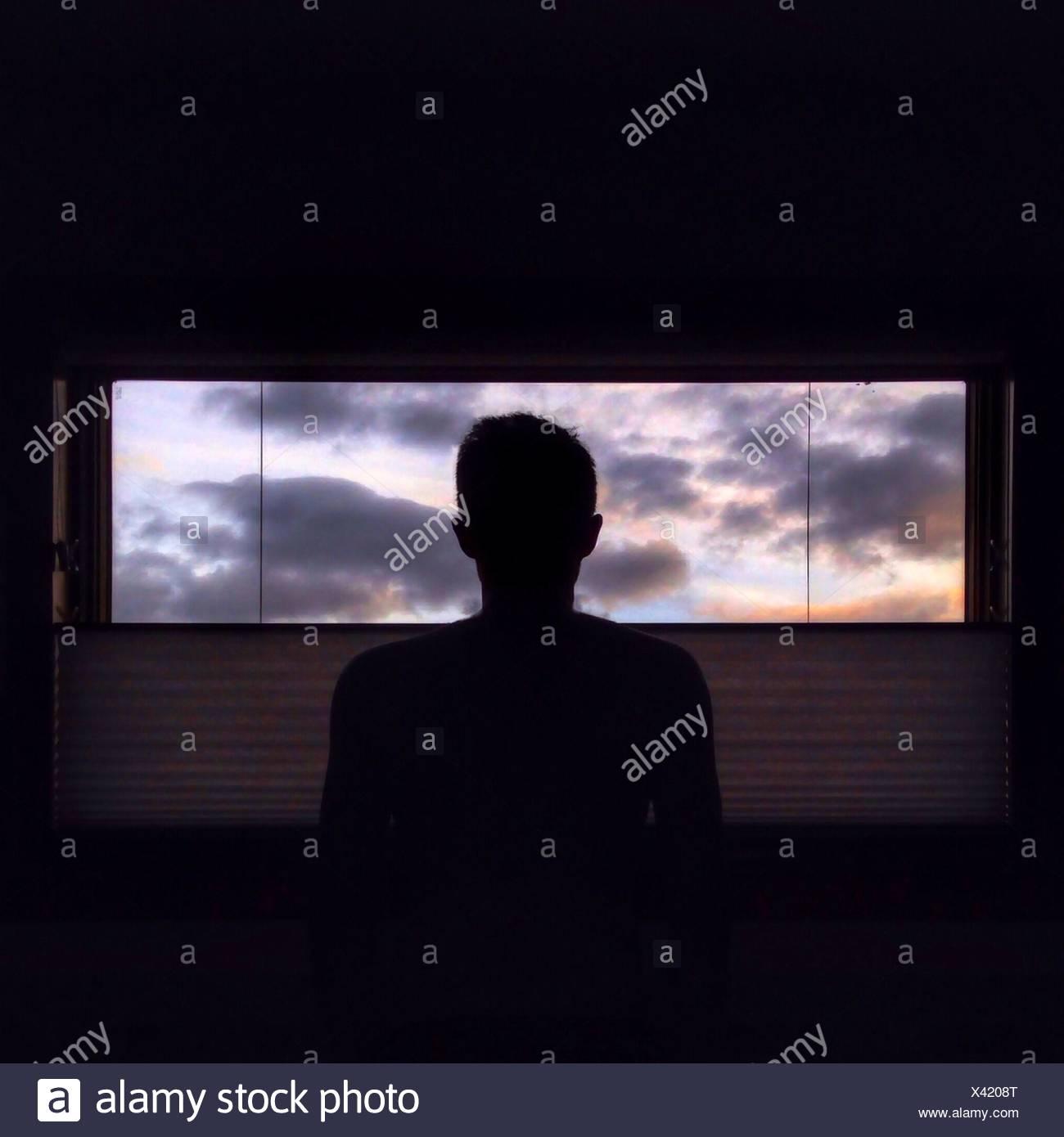 L'homme en regardant par la fenêtre Photo Stock