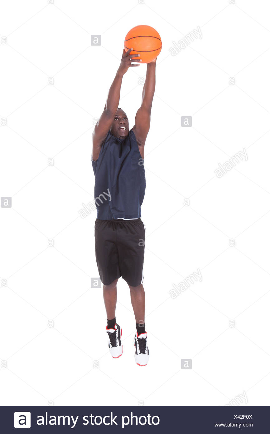 Jeune homme africain sautant avec le basket ball Over White
