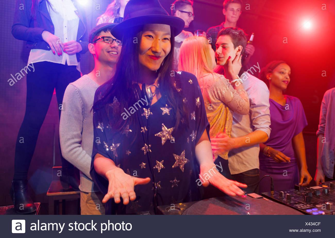 Mid adult woman DJing at party, les gens danser en arrière-plan Photo Stock