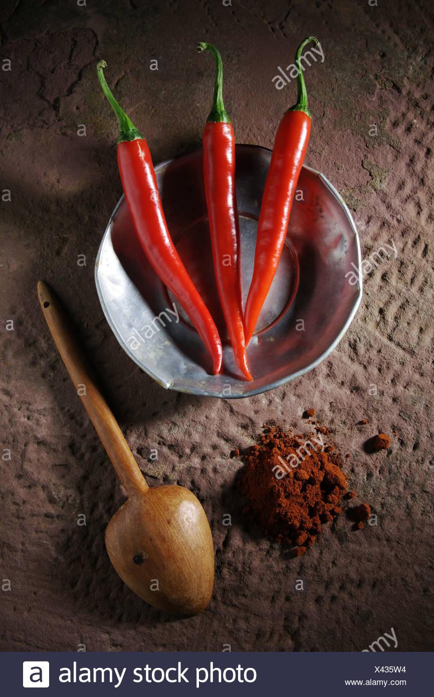 Trois piments forts (Capsicum) sur une plaque d'étain avec une cuillère en bois et la poudre de chili sur une surface en pierre rustique Photo Stock