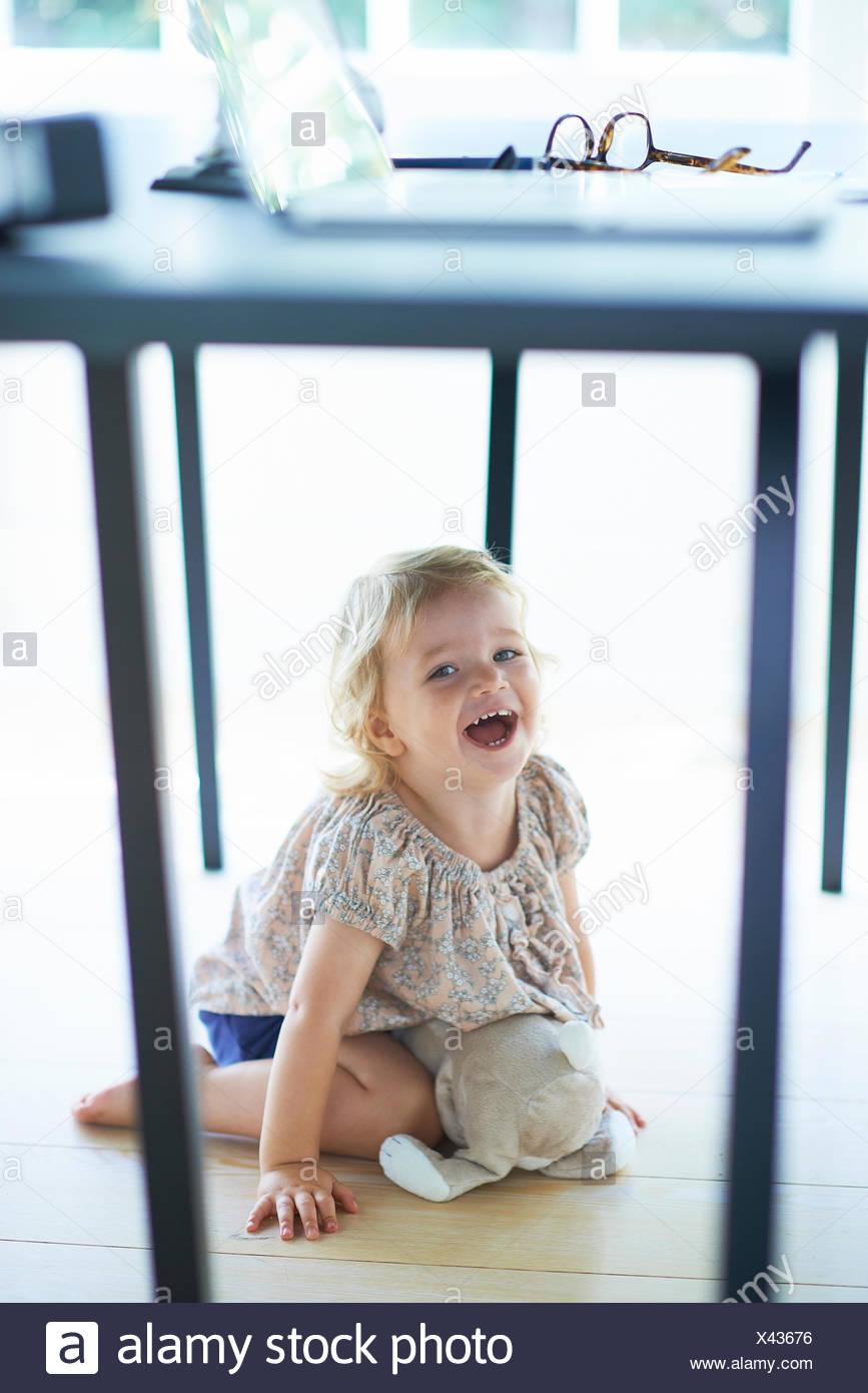 Female toddler cacher et rire sous table de salle à manger Photo Stock