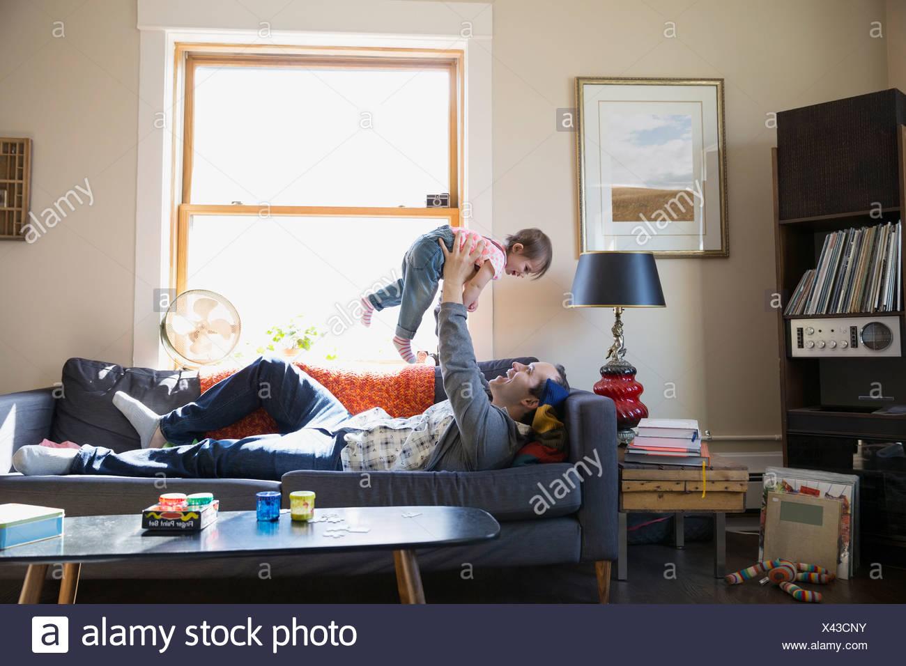 Père fille bébé de levage sur canapé de frais généraux Photo Stock
