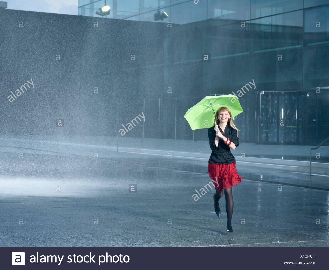 Une jeune femme tenant un parapluie vert sous la pluie Photo Stock