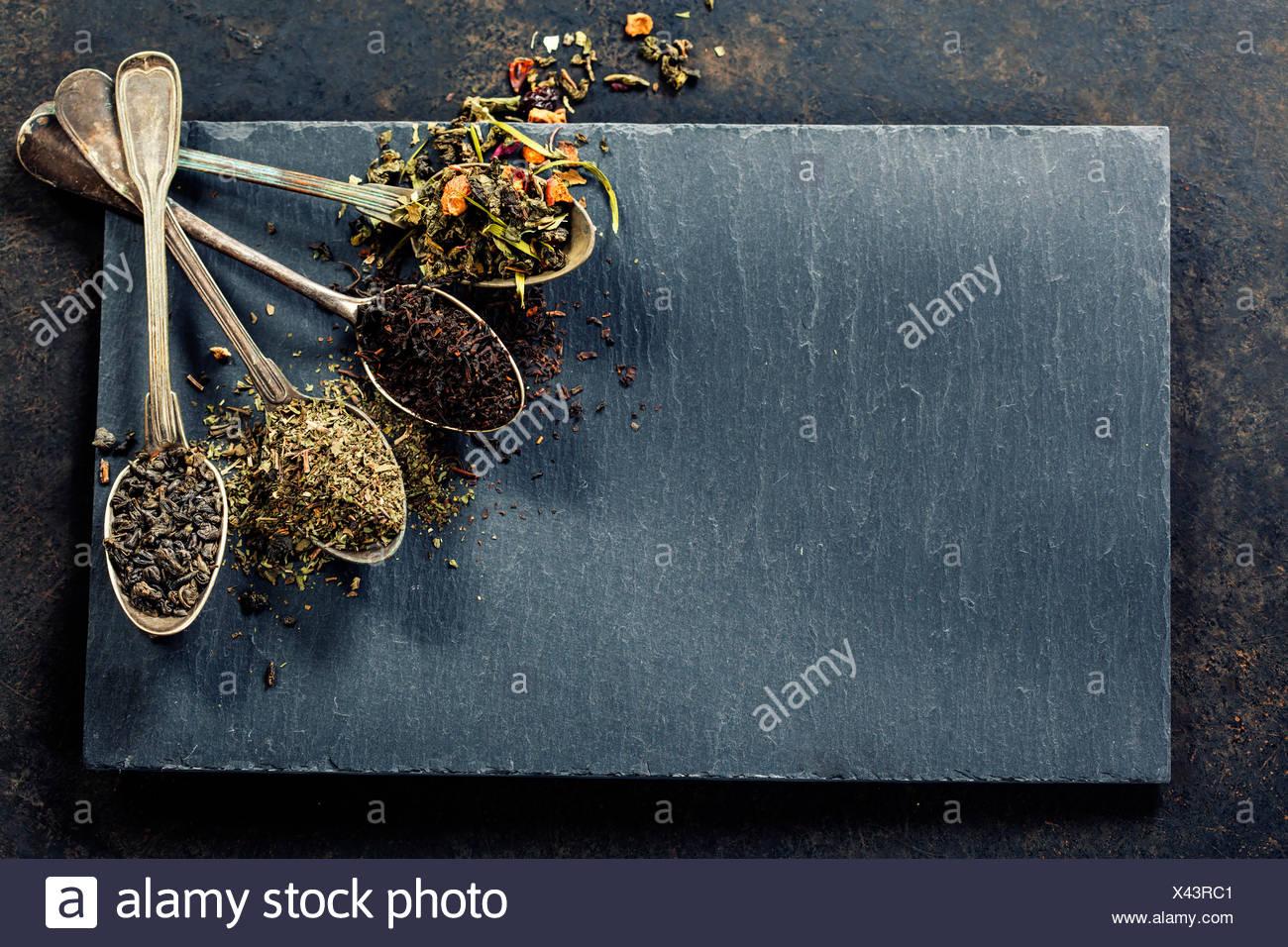 Plateau de composition avec différents types de thé et de vieilles cuillères sur fond sombre Photo Stock