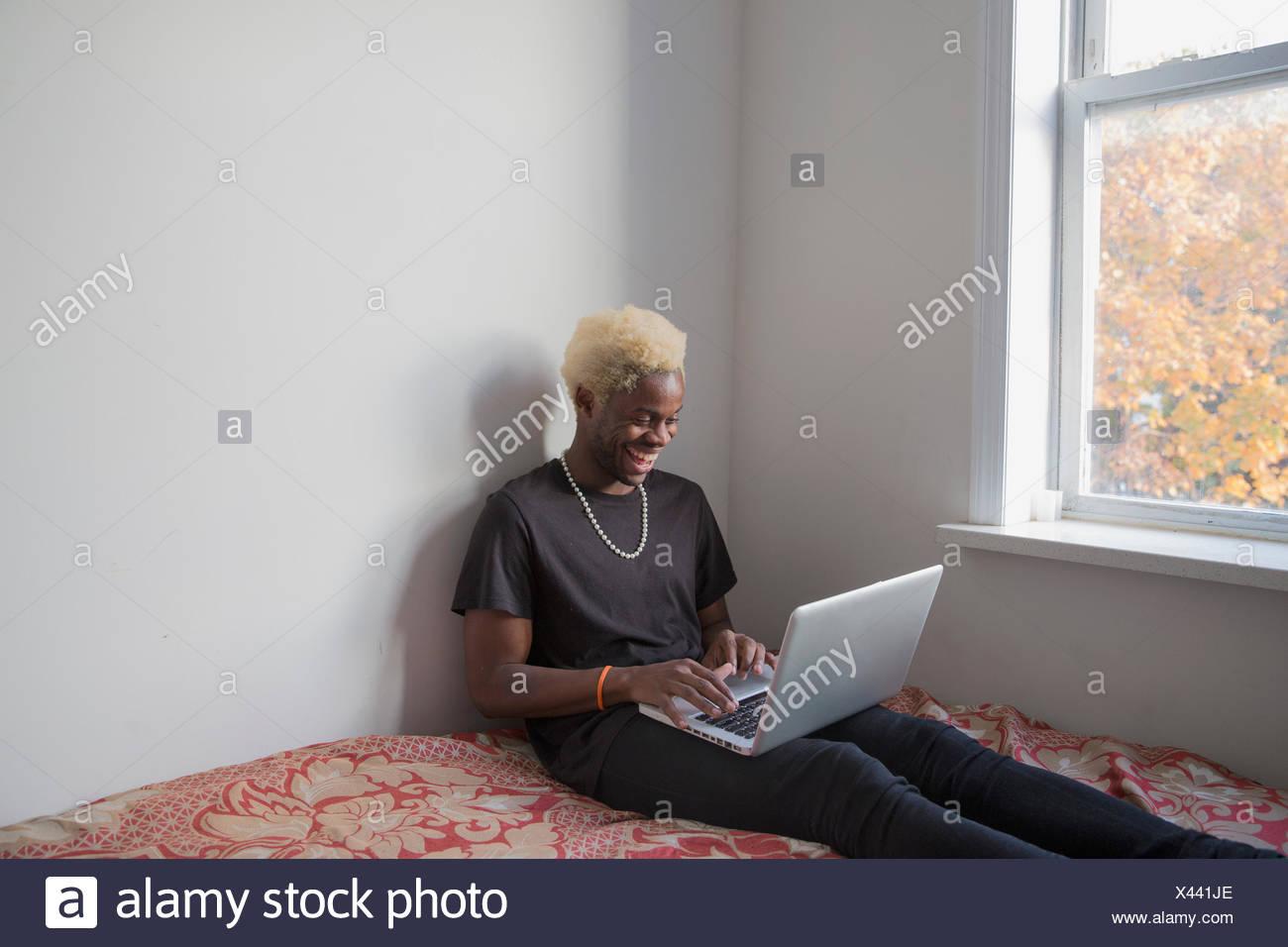 Jeune homme souriant comme il tape sur son ordinateur portable par une fenêtre à la maison Photo Stock